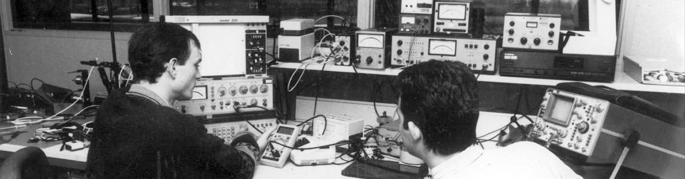 Historical photo of Clarity engineers using audio test equipment in the 1980s.